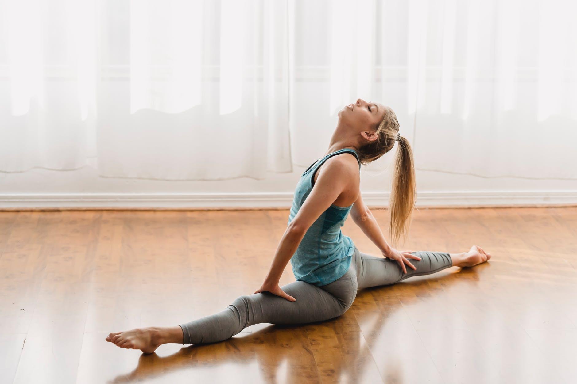 flexible young woman doing yoga in hanumanasana